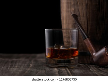 Glass of whiskey with ice cubes and vintage smoking pipe next to wooden barrel. Cognac and brandy drink