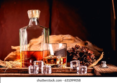 Glass of whiskey with ice decanter on wooden table.