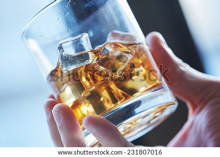 glass of whiskey with ice in his hand