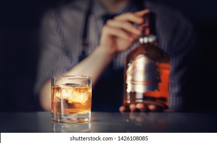 Glass of whiskey with ice is on bar, bartender ready to fill shot.