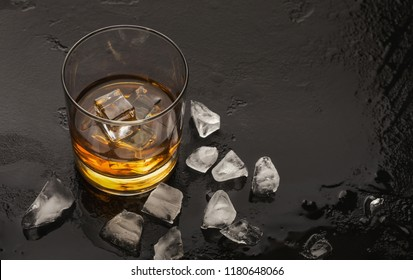 Glass of whiskey with ice on black background. Masculine weekend relaxation, copy space