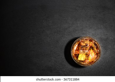 Glass of whiskey with ice on black background shot from above