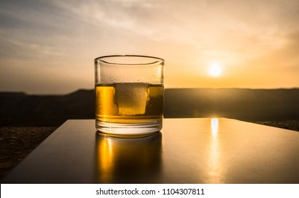 A glass of whiskey with ice on a sunset background or shot of whiskey at sunset dramatic sky on mountain landscape background. Selective focus