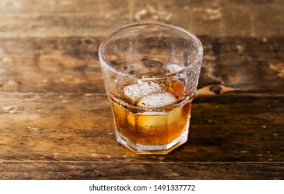 a glass of whiskey with ice on the table