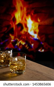 Glass of whiskey with ice on a wooden table in front of a fireplace