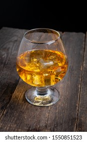 glass of whiskey with ice on wooden table