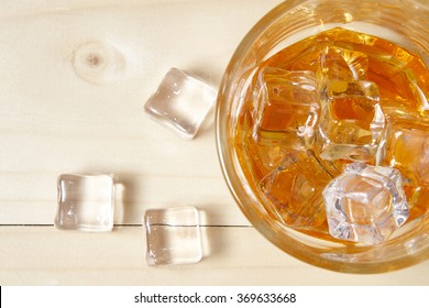 Glass of whiskey with ice on wooden table. Top view