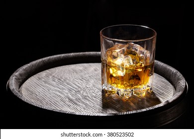 Glass of whiskey with ice on wooden barrel on black background