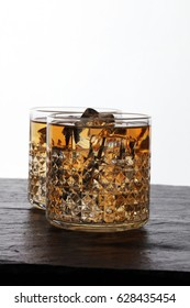 glass of whiskey with ice on a wooden
