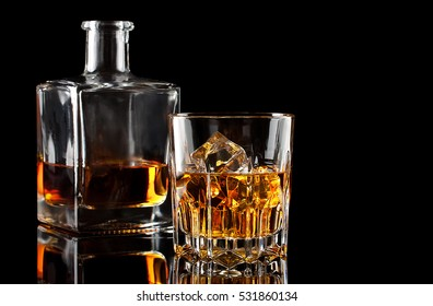Glass of the whiskey with ice and a square decanter isolated on a black background