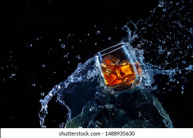 Glass of whiskey with ice .Water splash the glass.Creative photo glass of whiskey on stone with fog and black background.Copy space.Advertising shot