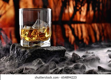 Glass of whiskey and ice.Creative photo glass of whiskey on stone with fog and sunset background.Copy space.Advertising shot