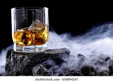 Glass of whiskey and ice.Creative photo glass of whiskey on stone with fog.Copy space.Advertising shot
