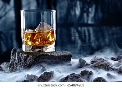 Glass of whiskey and ice.Creative photo glass of whiskey on stone with fog and cold background.Copy space.Advertising shot