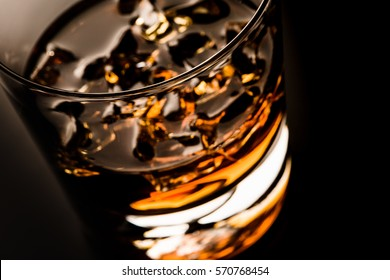 Glass of whiskey isolated on black background