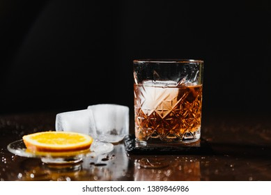 Glass of whiskey with lemon and ice on black bar counter. Whiskey glass on a dark background. Alcoholic cocktail with ice and lemon. Old fashion cognac glass with lemon and ice. Glass of cognac.