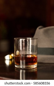 Glass of whiskey and men's watch on the wooden retro table