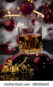 a glass of whiskey in the middle of the scene of Christmas decoration and gifts