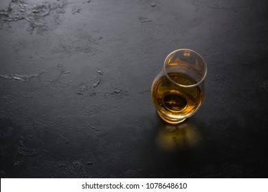 a glass of whiskey on a black background with space for text