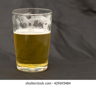 A glass of whiskey on a black background