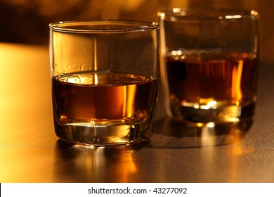Glass of whiskey on brown bar counter