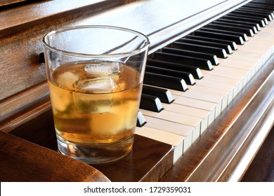 Glass of whiskey on the edge of a piano keyboard
