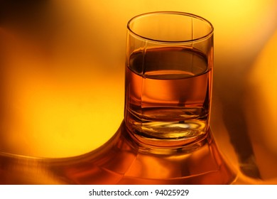 A glass of Whiskey on gold background