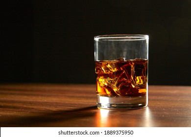 A Glass of whiskey on ice on wood table