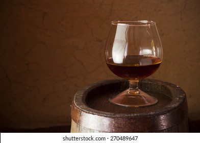 A glass of whiskey  on an old oak barrel