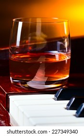 glass with whiskey on a old piano
