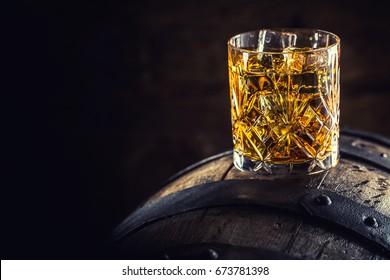 Glass of whiskey on old wooden barrel.