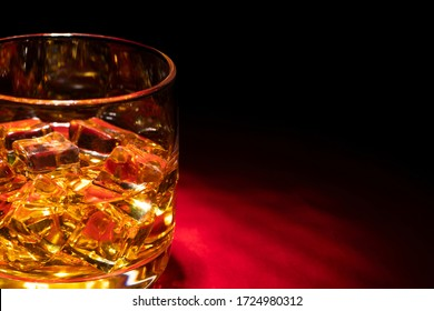 A glass of whiskey on the rocks on the red table. Side view