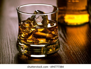Glass of whiskey on the rocks on a wooden table