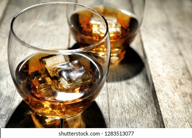 Glass of whiskey on wooden table, closeup