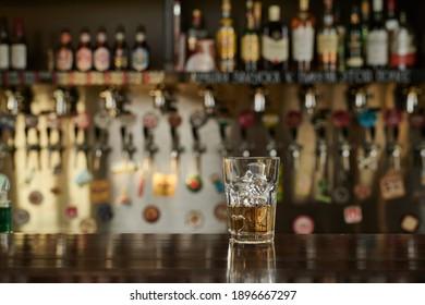 Glas Whiskey auf einem Holztisch. Alcoholismus Konzept.Addicting to alkoholische Getränke.Nahaufnahme von Kristallglas Whiskey, Brandy oder Scotch auf dem Tisch. Hinter Menschen, die in Bar sitzen, Kommunikation