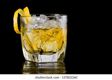 glass of whiskey over ice served on a dark bar garnished with a twist
