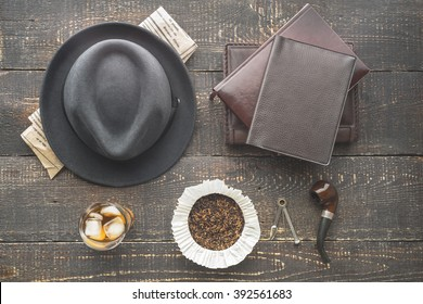 Glass of whiskey , pipe  , hat and newspaper on the wooden table top view