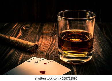 Glass of whiskey and playing cards with cuban cigar on the wooden table. Angle view, image vignetting and the orange-blue toning, identification cards ace Russian letter