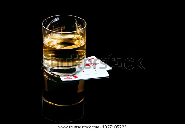 Glass of whiskey and playing cards on the black background