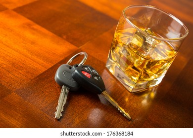 Glass of whiskey and set of car keys on table, drinking and driving