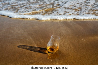 a glass of whiskey single malt on the sand washed by the waves, a glass of tasting, relax on the beach, vacation