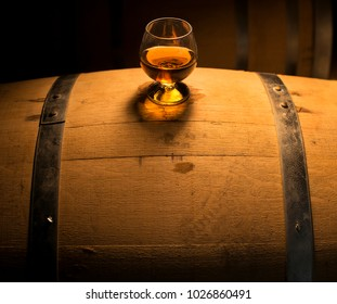 A glass of whiskey sits atop of a whiskey barrel that is aging product. The look of the photo has a vintage feel with a modern spirit.
