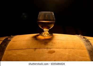 A glass of whiskey sits atop of whiskey barrel.
