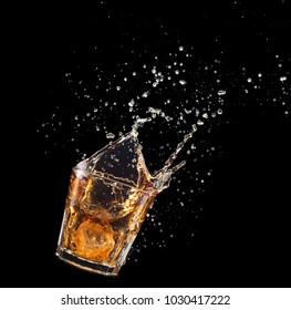 Glass of whiskey with splash isolated on black background