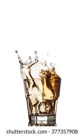 Glass of whiskey with splash, isolated on white background.
