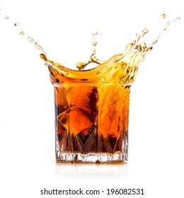 Glass with whiskey splash on white background