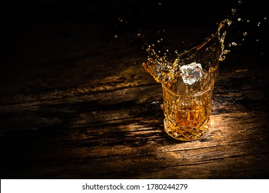 A glass of whiskey with splashes from the ice cube. glass with a splash of whisky on wooden background.