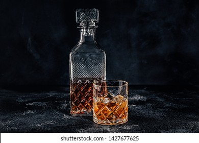 Glass of the whiskey with a square decanter on a black stone background.