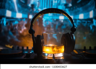 Glass with whisky with ice cube inside on dj controller at nightclub. Dj earphones on a glass of whilsky at music party in nightclub with disco lights. Selective focus