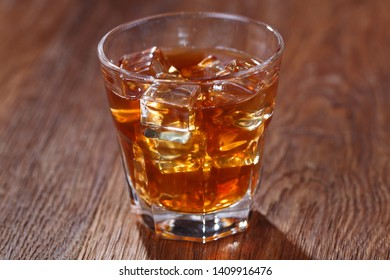 Glass of whisky and ice on wooden bar table